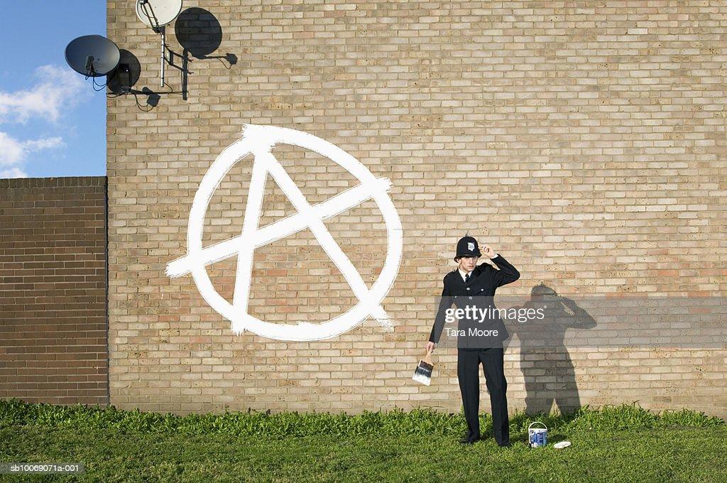 Policeman painting graffiti on wall : Stockfoto