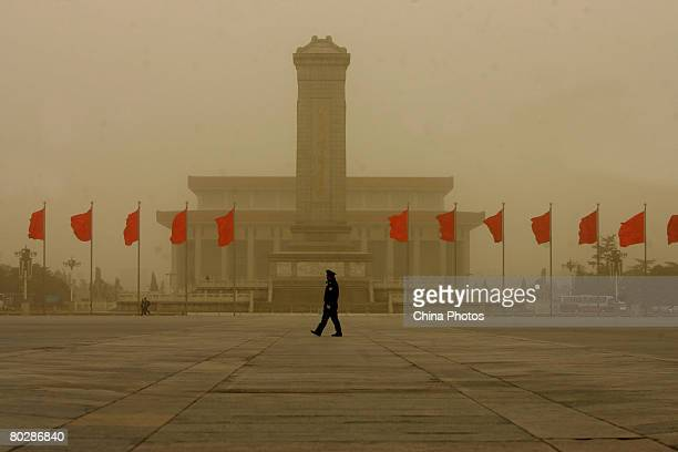 Policeman patrols on the Tiananmen Square as floating dust changed color of the sky to orange on March 18, 2008 in Beijing, China. The blowing sand...