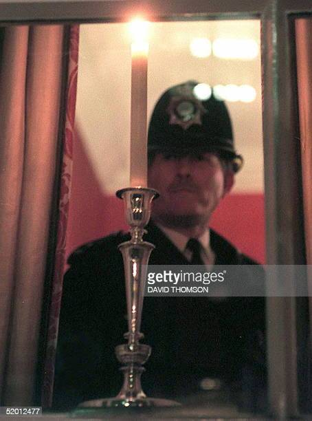 A policeman places a candle on a window ledge at number 10 Downing street 13 March which the Prime Minister John Major and his wife Norma lit in...