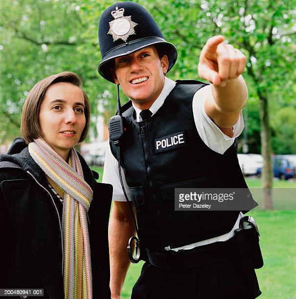 policeman pointing beside woman - police force stock pictures, royalty-free photos & images