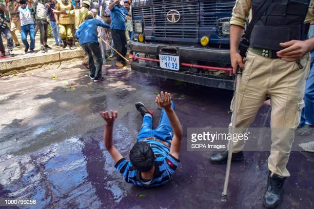 JK policeman points his baton at a protesting Kashmiri government teacher in Srinagar on Tuesday Police used water cannons batons and detained dozens...
