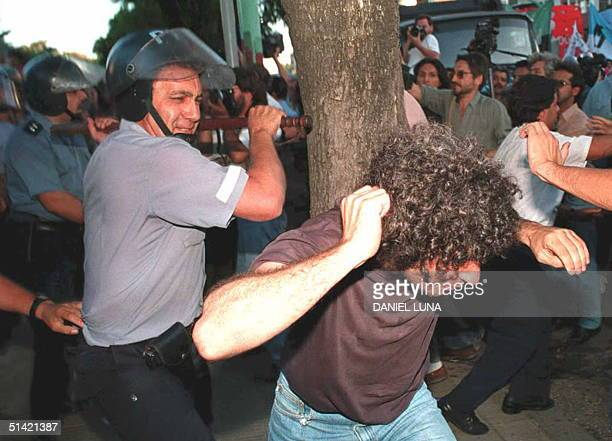 A policeman prepares to hit a demonstrator 23 March outside the Argentine Navy's School of Mechanics in Buenos Aires The demonstrators and the...