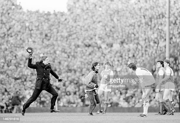 A policeman pursues a football hooligan who has run onto the pitch during the match between Arsenal and Tottenham Hotspur at Highbury Stadium circa...