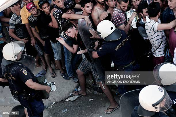 A policeman pushes a migrant as hundreds wait to complete a registration procedure by the police at a stadium on the Greek island of Kos on August 12...
