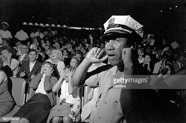 A Policeman puts his fingers in his ears to block out the noise as the Beatles perform on stage during their tour of America September 1964 S07757