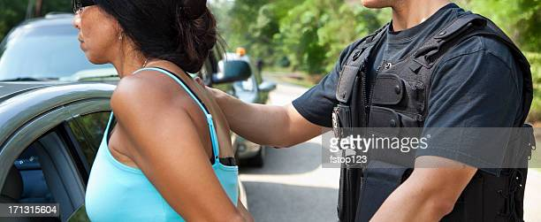 Policeman putting handcuffs on woman beside vehicles