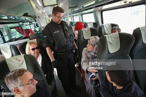 A policeman questions passengers and asks migrants without a valid visa to disembark from a regular train that had arrived from Vienna Austria on...