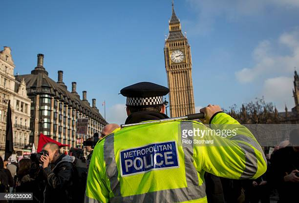 A policeman raises his baton as a march against student university fees passes the Houses of Parliament on November 19 2014 in London England A...