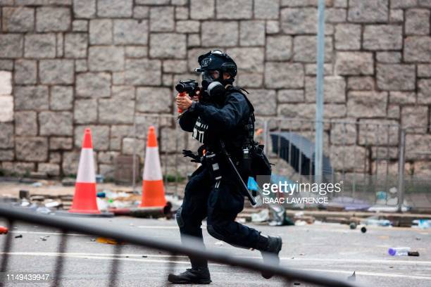 A policeman raises his weapon during a rally by protesters against a controversial extradition law proposal outside the government headquarters in...