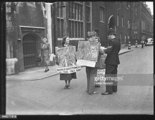 A policeman remonstrates with artists who are demonstrating against atomic bombs outside the house where the North Atlantic Treaty Council are...