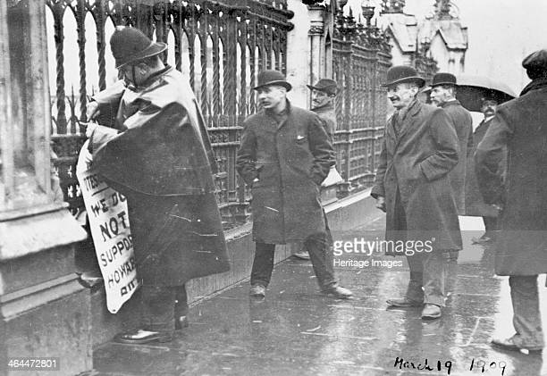 A policeman removes a suffragette poster from the railings in the vicinity of the House of Commons London 19th March 1909 Plastering important places...