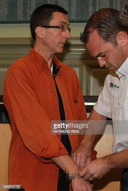 A policeman removes the handcuffs of Frantz Diguelman the lover of a Madagascan woman who allegedly tricked him into killing her husband with a...