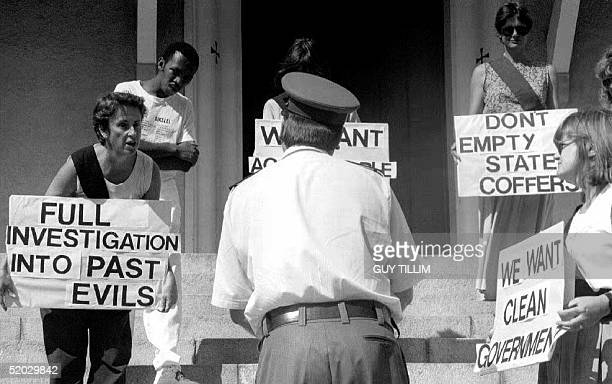A policeman responds to members of the Black Sash antiapartheid organization protesting 29 January 1993 in Cape Town before the opening of Parliament...