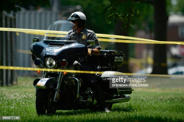A policeman rides a motorcycle next to the scene after a shooting during a practice of the Republican congressional baseball at Eugene Simpson...