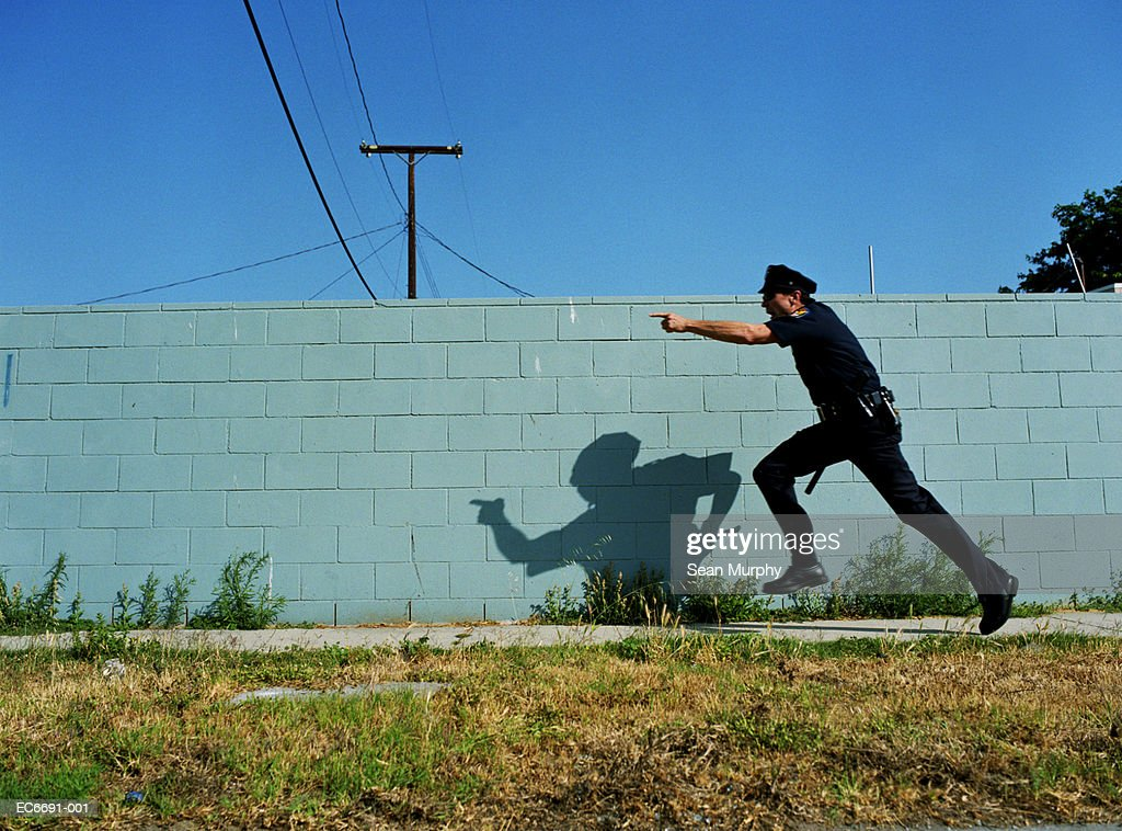 Policeman running next to cement wall, yelling and pointing finger : Stock Photo
