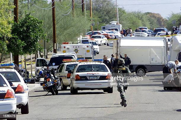 A policeman runs down a street after a gunman opened fire inside a classroom of the College of Nursing at the University of Arizona October 28 2002...