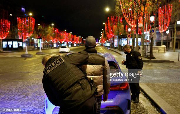 Policeman search a man as French police officers of the anti-crime squad, Brigade Anti-Criminalite de nuit perform a road check on the Champs Elysees...
