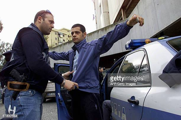 Policeman searches a man suspected of being in the mafia during a huge ongoing operation involving hundreds of police officers, early 07 December...