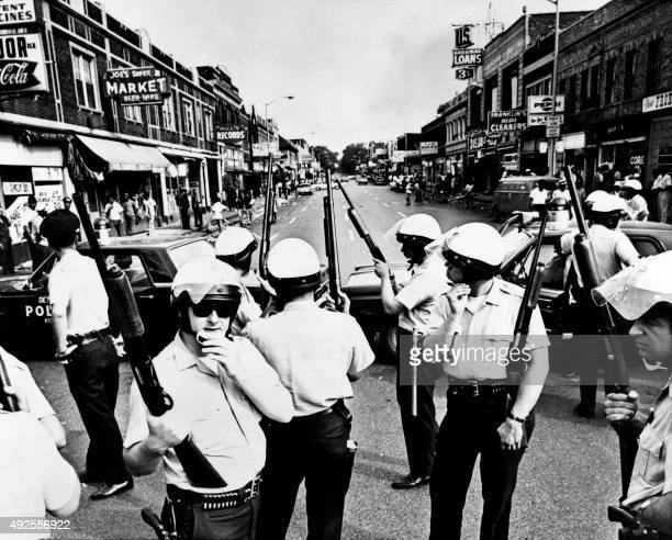 A policeman searches black suspects in a Detroit street on July 25 1967 as buildings are burning during riots that erupted in Detroit following a...