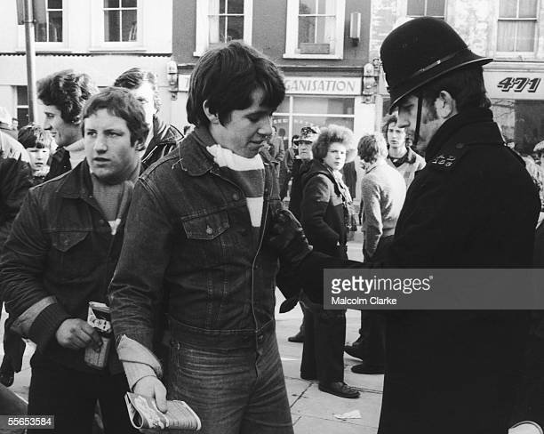A policeman searches fans as they enter Stamford Bridge football ground for a match between Chelsea and Manchester United 11th February 1978
