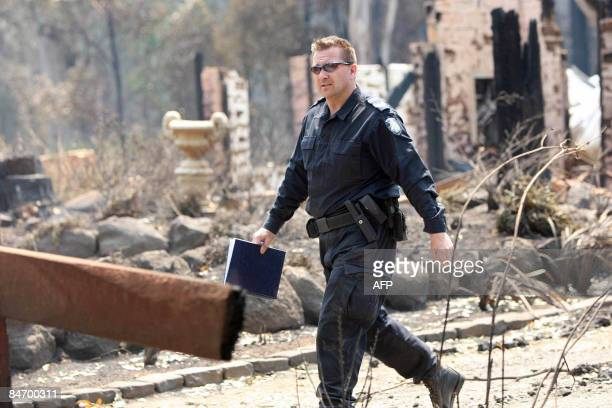 A policeman searches through the ruins and remaining houses in Kinglake to establish the numbers of those injured or missing from the raging...