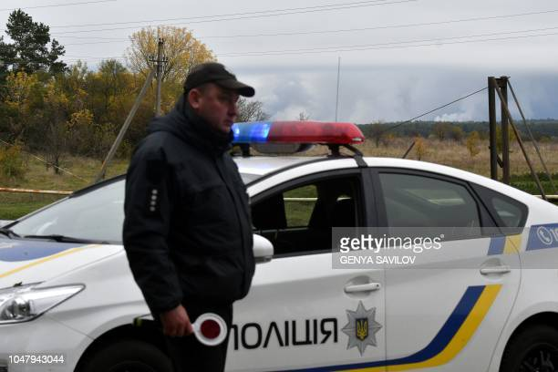 A policeman secures road near Zaudaika village in Ukraines northern Chernihiv Region on October 9 as smoke from explosions at the an ammunition depot...
