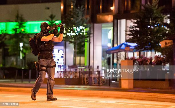 TOPSHOT A policeman secures the area around the shopping mall Olympia Einkaufzentrum OEZ in Munich on July 22 2016 after gunmen went on a shooting...