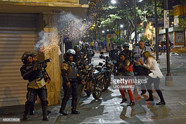 A policeman shoots tear gas to antigovernment protesters during clashes in Caracas on June 12 2014 AFP PHOTO/ LEO RAMIREZ