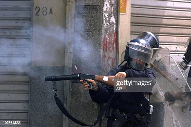 A policeman shoots teargas from an angle in Algeria's northeastern Kabylie region 28 April 2001 Renewed riots broke in Algeria's northeastern Kabylie...