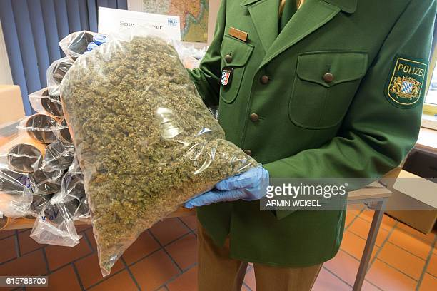 A policeman shows a bag with seized marijuana during a press conference in Passau southern Germany on October 20 2016 230kg Marjuana were found in...