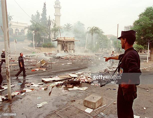 A Policeman shows the damages after a protest march in a street of TiziOuzou 26 June after the killing of the popular singer and Berber rights...