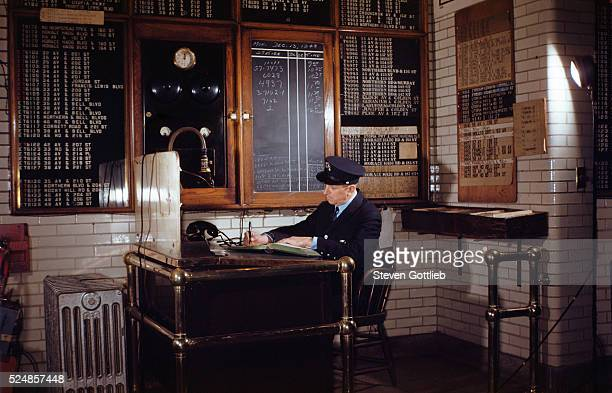 A policeman sits at a desk and writes in a book in a police station