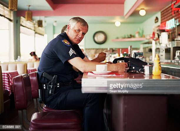 Policeman sitting having coffee at bar in diner