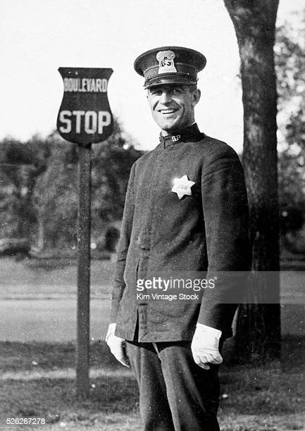 Policeman smiles by a bus stop sign ca 1925