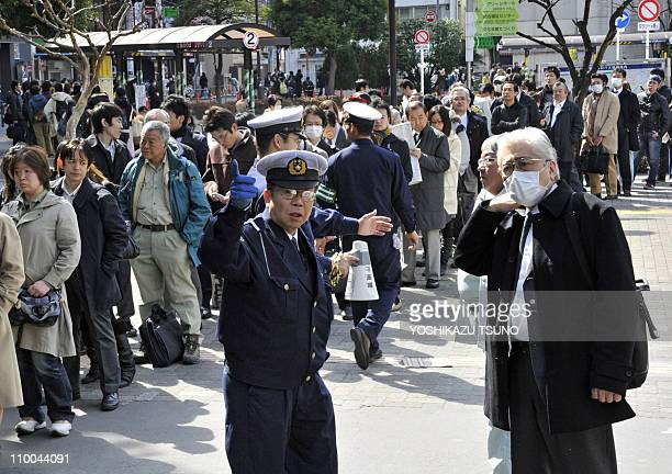 Policeman speaks to a commuters as others queue waiting for train services to resume at Tokyo's Chofu station on March 14, 2011 as rail services...