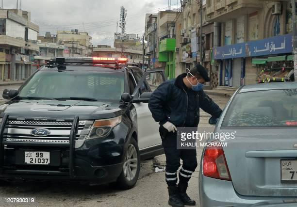 A policeman speaks to a driver at a checkpoint in the Jordanian capital Amman during a nationawide curfew imposed by the authorities in order to...