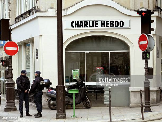 """Policeman stand in front of the satirical French weekly """"Charlie Hebdo""""'s headquarters, 08 February 2006 in Paris. Charlie Hebdo printed all 12 of..."""