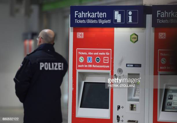 Policeman stand near a tickt station as they secure a crime scene after an axe attack on passengers at the main train station on March 9 2017 in...