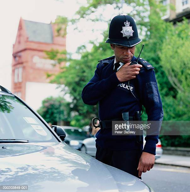 policeman standing by car using radio - english culture stock pictures, royalty-free photos & images