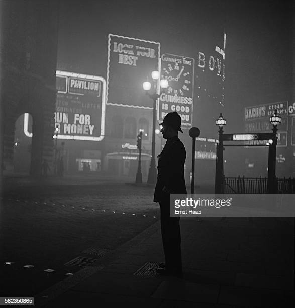Policeman standing in Piccadilly Circus at night, London, circa 1953.
