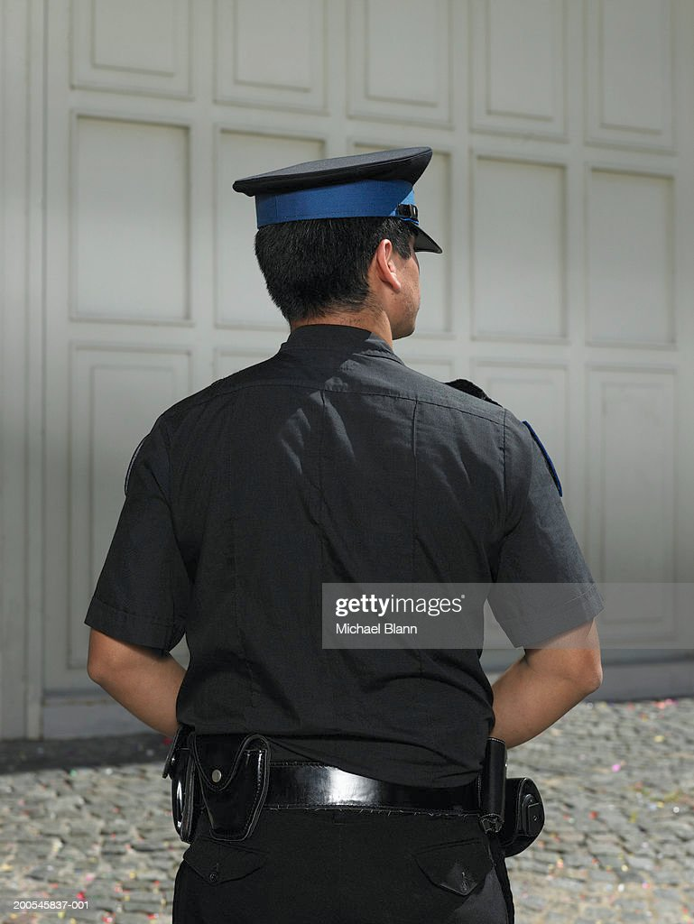 Policeman standing in street, rear view : Stock Photo