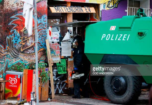 A policeman standing nest to an armoured police vehicle uses a chain saw to enter the main door of the squatted building at Liebig Street 34 at the...