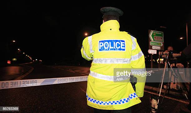 Policeman stands along a road near the Massereene army base where two military personnle were killed in County Antrim, near Belfast on March 7, 2009....