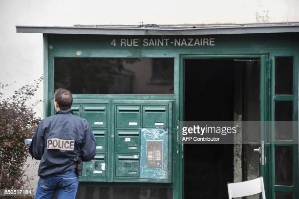 A policeman stands at the entrance of a building where a fire broke out overnight killing five people in Mulhouse on October 2 2017 / AFP PHOTO /...
