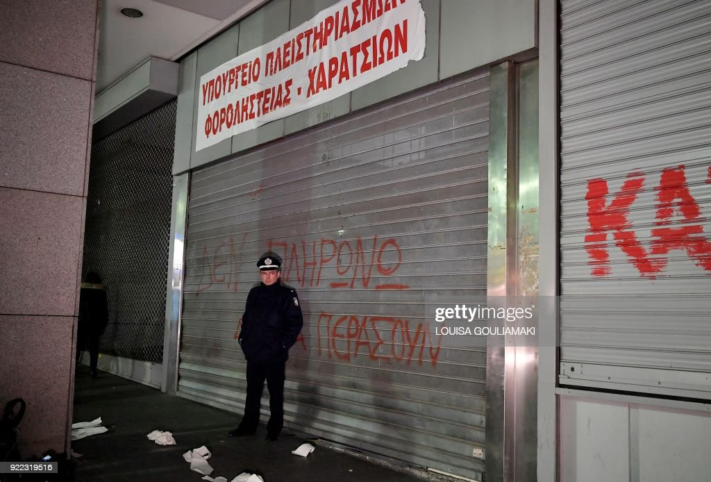 A policeman stands at the entrance of the Greek Finance Ministry in Athens under a banner set up by Communist-affiliated All-Workers Militant Front (PAME) unionists reading 'Ministry of foreclosures and tax thieves' at the Greek Finance Ministry in Athens on February 21, 2018, after a protest against property auctions demanded by Greece's creditors as part of the Greek austerity measures. /