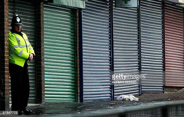 A policeman stands beside a row of closed shops near the area where a shooting happened in the earlier 02 January 2003 in Birmingham Two teenage...