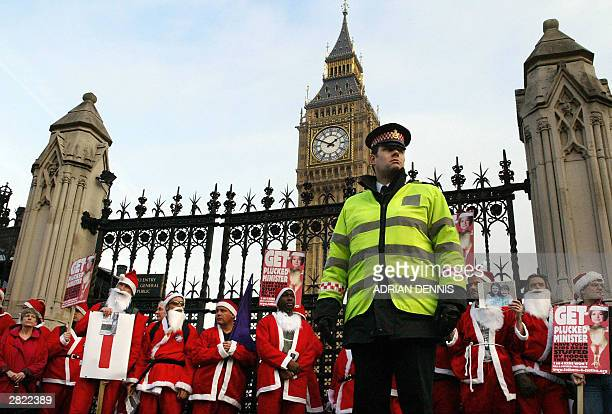 Policeman stands beside protesters dressed as Father Christmas' outside The Houses of Parliament during a march in central London 19 December 2003....