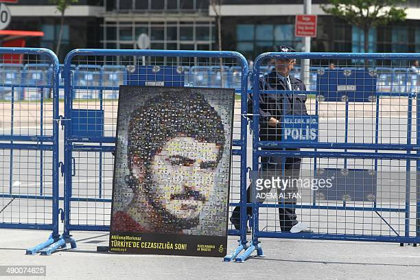 A policeman stands by a portrait of late Ali Ihsan Korkmaz outside a courthouse in Kayseri on May 12 2014 Emel Korkmaz the mother of Ali Ihsan...