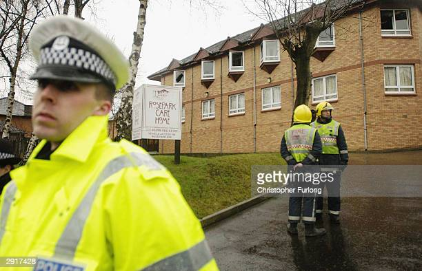 A policeman stands guard after a fire at Rose Park care home on January 31 2004 in Uddingston near Glasgow Scotland The fire broke out in the early...