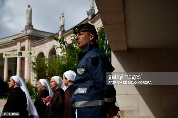 Policeman stands guard as a group of nuns walk past in Fatima, central Portugal, on May 11, 2017. Two of the three child shepherds who reported...